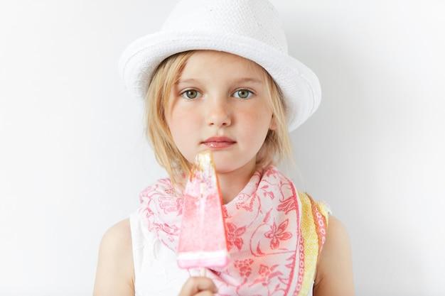 Bambina bionda che indossa cappello bianco e mangia il gelato
