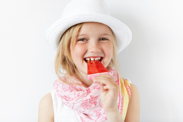Little blonde girl wearing white hat and eating ice cream