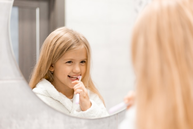 Little blonde girl in a white bathrobe brushes her teeth in front of the bathroom mirror