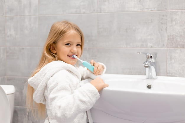 Little blonde girl in a white bathrobe brushes her teeth with an electric toothbrush in front