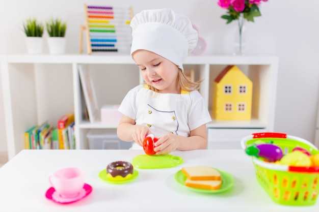 Little blonde girl in white cook uniform playing with toy fruits and vegetables at home, in kindergaten or preschool. game activities to play with a child at home