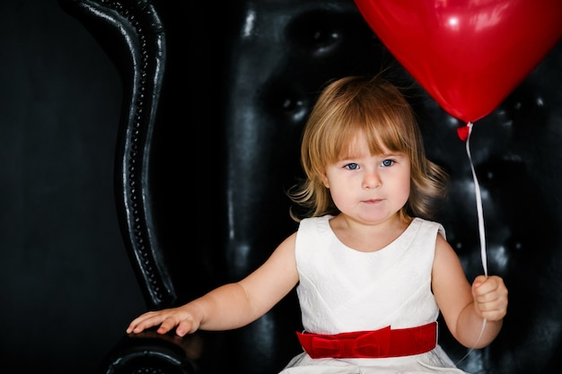 Little blonde girl in white dress with red ribbon sitting on the armchair with red heart balloon on the  valentines day