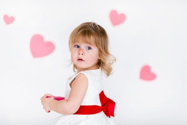 Little blonde girl in white dress with red ribbon on white floor with pink hearts on the  valentines day