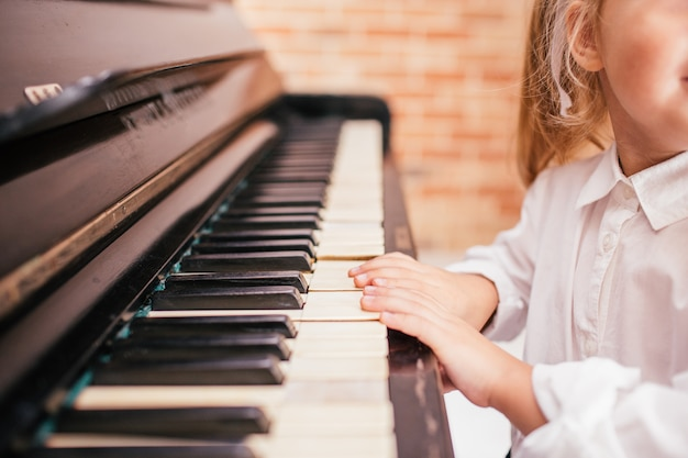 Little blonde girl in white trying to play on dark vintage piano, closeup