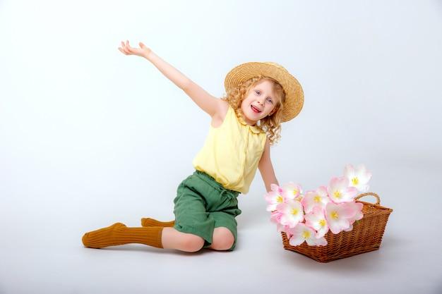 春のピンクの花のバスケットと小さなブロンドの女の子