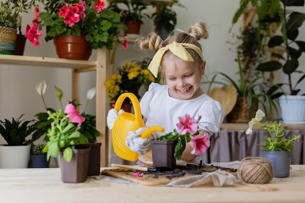 彼女の頭の植物と移植と水室内の花に弓を持つ小さなブロンドの女の子