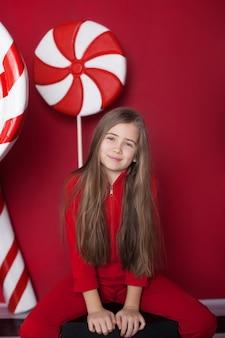 孤立した赤い背景に巨大なクリスマスキャンディーを持つ小さなブロンドの女の子
