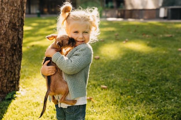 屋外で子犬と小さなブロンドの女の子