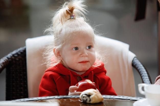 尾を持つ小さなブロンドの女の子は、カフェのテーブルでリンゴを食べます。