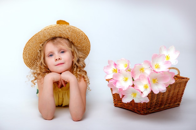 Little blonde girl with a basket of spring pink flowers
