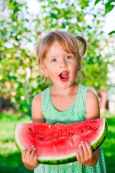 Little blonde girl with big slice watermelon in summer time in park, outdoor. surprise child. oops, wow.