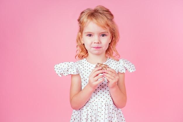 분홍색 배경에 스튜디오에서 4-5세의 완두콩을 입은 곱슬머리 헤어스타일을 한 어린 금발 소녀는 생일 파티에서 새해 쿠키를 축하하고 아이들을 격려하며 분홍색 배경에 진저브레드를 먹습니다.
