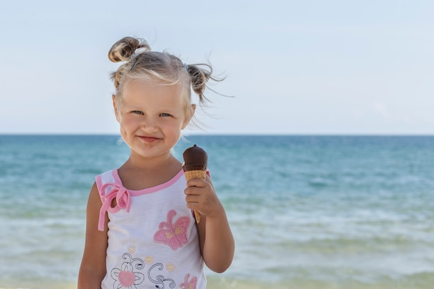 Little blonde girl with a dirty mouth from chocolate on the beach holds a chocolate ice cream in her hand and smiles