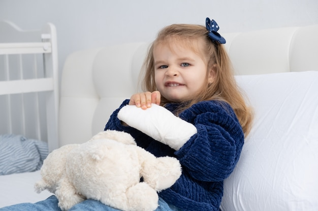 Little blonde girl with hand in cast sitting in bed.