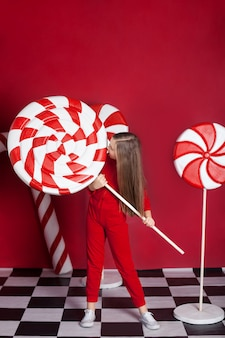 Little blonde girl with huge christmas candy on an isolated red wall.
