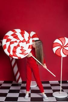孤立した赤い壁に巨大なクリスマスキャンディーと小さなブロンドの女の子。