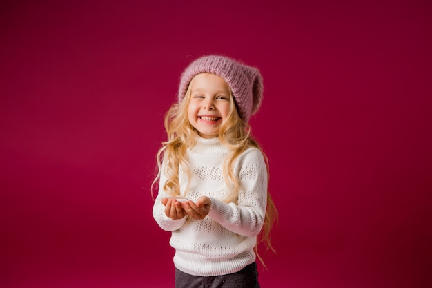 Little blonde girl with knitted hat and sweater plays with the snow