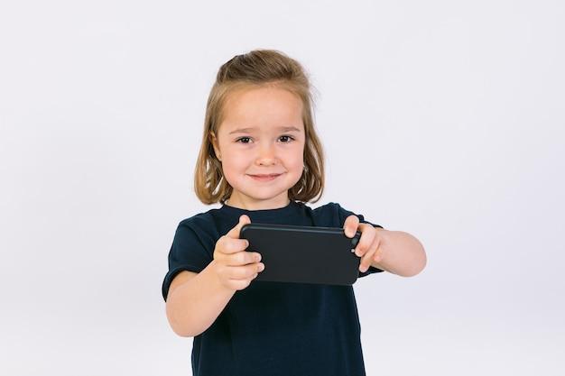 Маленькая блондинка с мобильным телефоном в руках, жестикулируя