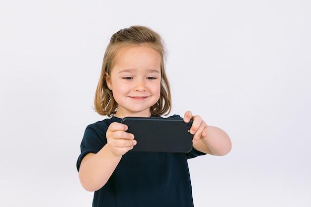Маленькая блондинка с мобильным телефоном в руках, играя в игру