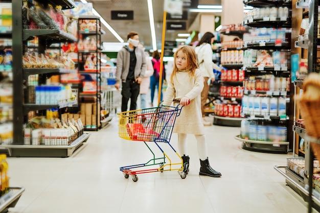 スーパーマーケットの棚の近くにトロリーを持つ小さなブロンドの女の子