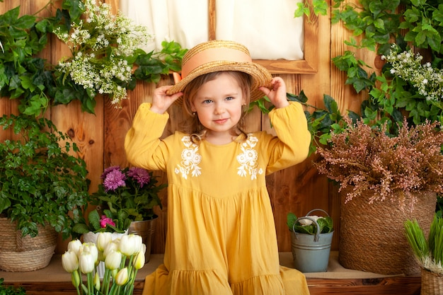 Little blonde girl in a yellow dress smiles and holds on to straw hat. concept of childhood. gardening. portrait of a beautiful kid in spring garden. children play outdoors. spring concept, nature