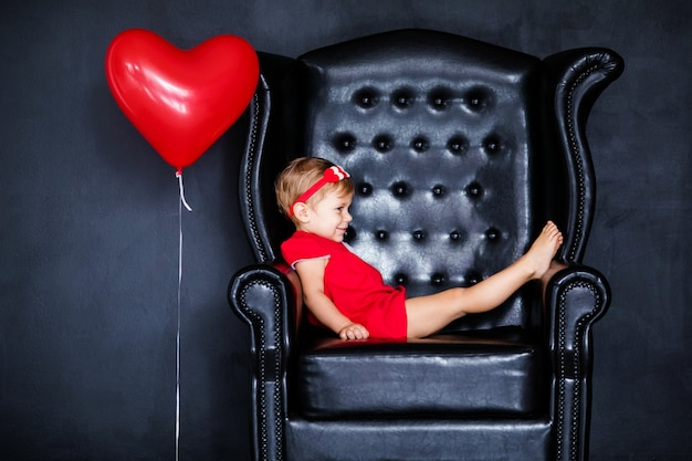 Little blonde girlin red dress with red wreath with hearts sitting on the armchair with red heart balloon on the  valentines day