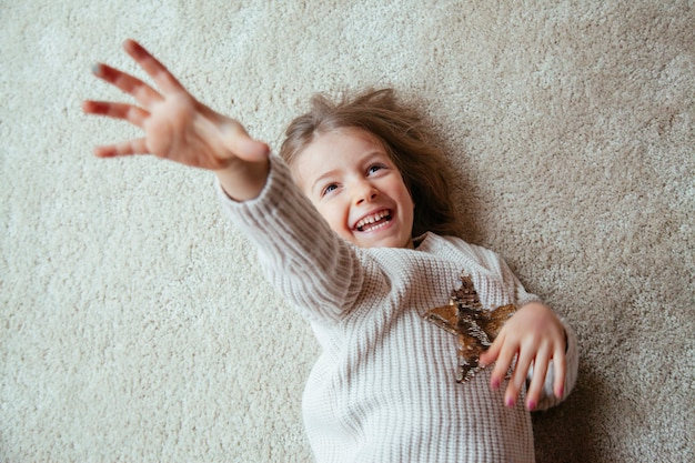 Little blonde kid on the floor with tickles