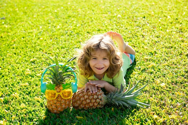 Little blonde kid hugging pineapple on nature background childhood healthy nutrition advertising clo...
