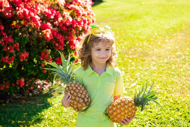 Little blonde kid hugging pineapple on nature background. childhood, healthy nutrition, advertising. close up kids funny face, copy space.