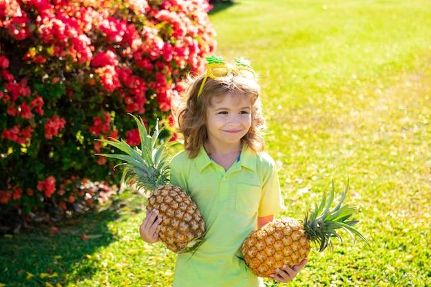自然の背景にパイナップルを抱き締める小さな金髪の子供。子供の頃、健康的な栄養、広告。子供の変な顔をクローズアップ、スペースをコピーします。