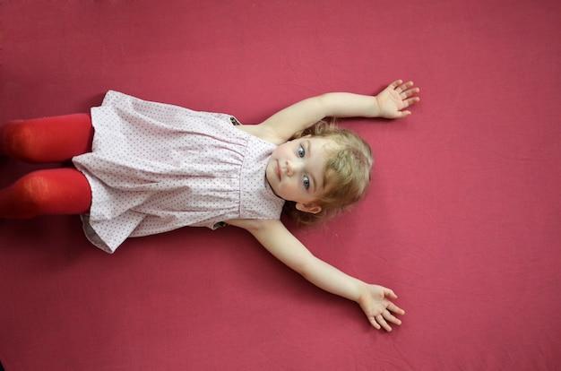 Маленькая блондинка лежа на темно-розовом фоне.