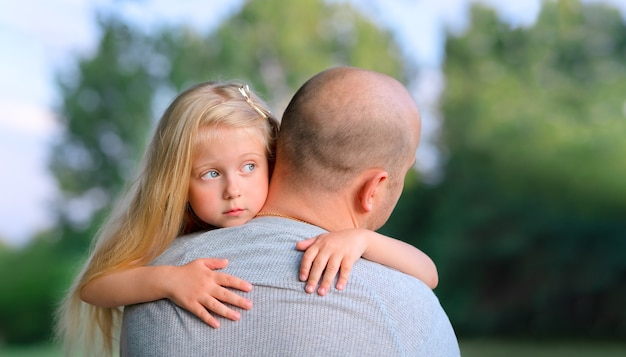 Маленькая блондинка грустная дочь обнимает своего отца