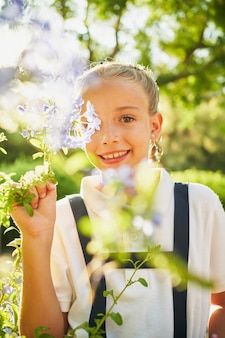 小さな金髪のスペインの女の子がカメラに微笑んで植物と花の間に立っています