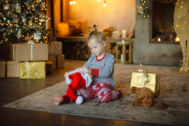 Little blonde toddler girl in christmas pajamas trying on santa's hat sitting at home on the carpet.