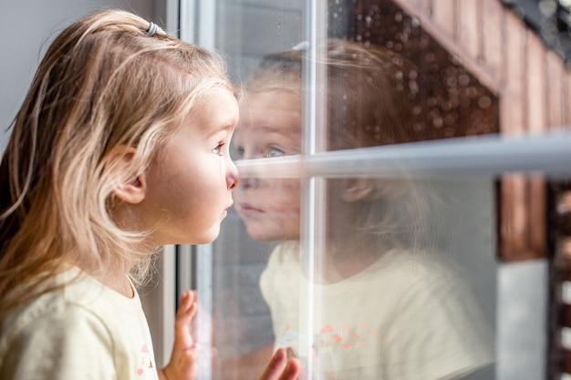 Маленькая белокурая девушка малыша смотря через окно с дождем падает на его. крупным планом портрет.