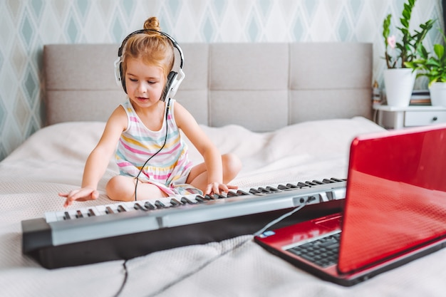 小さな金髪の幼児の女の子は、ラップトップでオンラインレッスン中に自宅で古典的なデジタルピアノを弾きます。