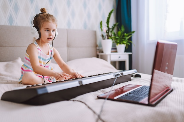 Little blonde toddler girl play classic digital piano at home during online lesson with laptop. online education concept, quarantine.