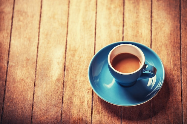 Little blue cup of the coffee on a wooden table