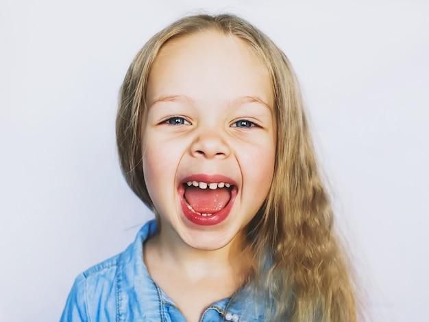Маленькая голубоглазая красивая девочка смеется с открытым ртом