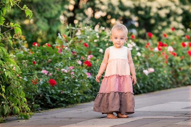 小さな青い目の女の子は、長いヴィンテージのリネンのドレスを着て夏に咲く庭を歩きます