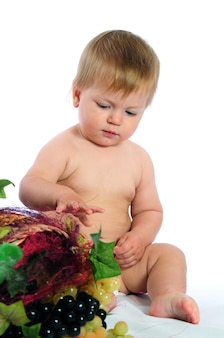 Little blue eyes baby boy sitting near wicker basket and holding grape in hands