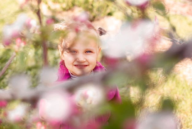 Little blueeyed blond girl in pink looks at camera from behind branches of a flowering tree