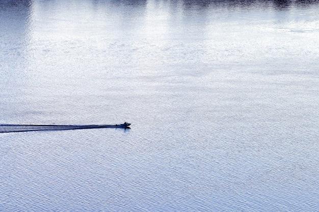 Маленькая лодка плывет по реке. рыболовный катер возле городской бухты. красивая вечерняя водная гладь. минимальный водный пейзаж.