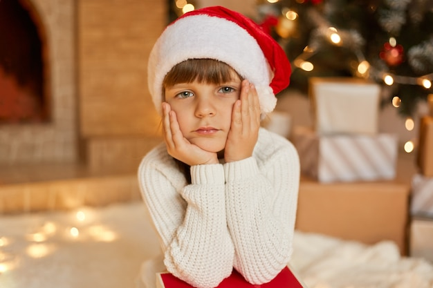 Little bored girl waiting for christmas, sitting in festive living room, keeping hands on cheek, looks at camera with sad expression, wearing white sweater and red santa hat.