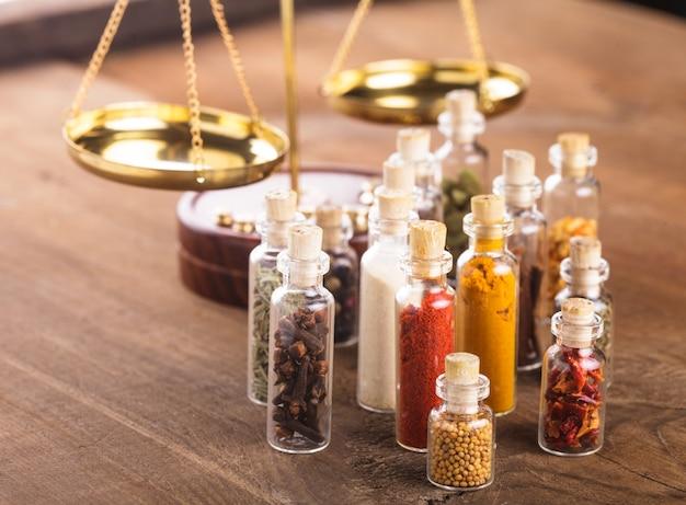 Бутылочки со специями и чешуей на столе