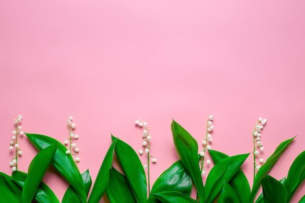 Маленькие букеты и зеленые листья ландыша в качестве цветочной каймы с плоской копией пространства ...