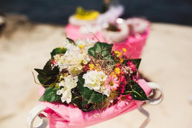ピンクと白の畑の花の小さな花束がテーブルに横たわっています
