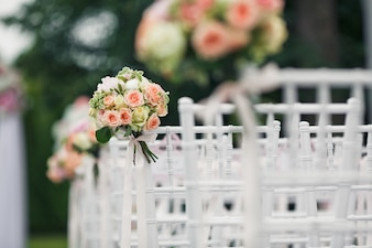 Little bouquets twined to the backs of white chairs