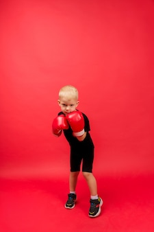 Little boxer boy makes a punch in red boxing gloves on red