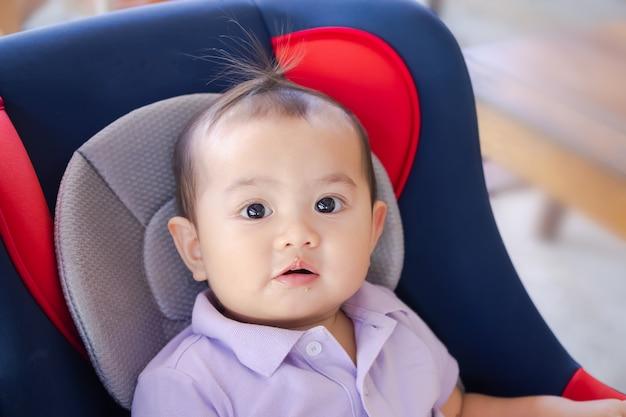 車の座席に座っている口の汚れたキャンディーを持つ小さな男の子1歳の赤ちゃん。本物のかわいい赤ちゃんアジアのタイ。母と子の概念。